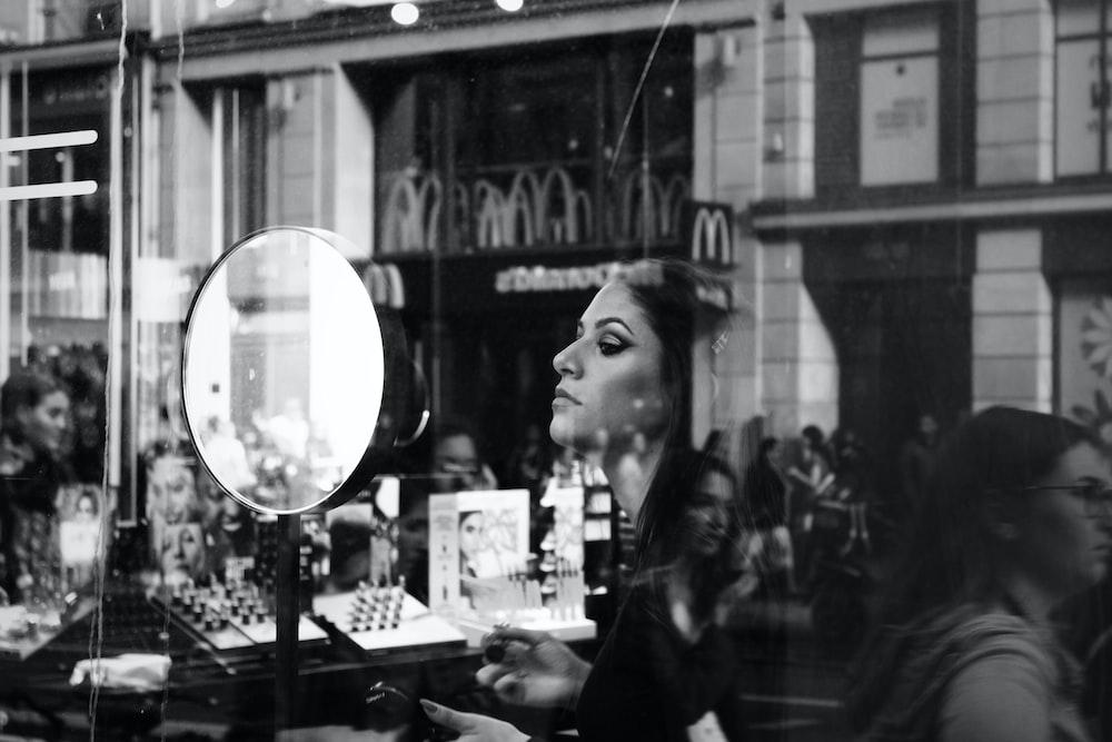 woman in black long sleeve shirt standing near glass window
