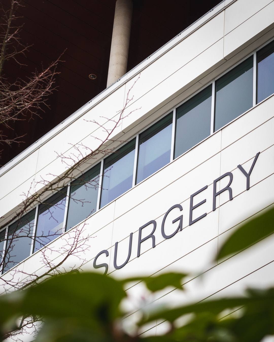 outside hospital building wall with sign saying surgery
