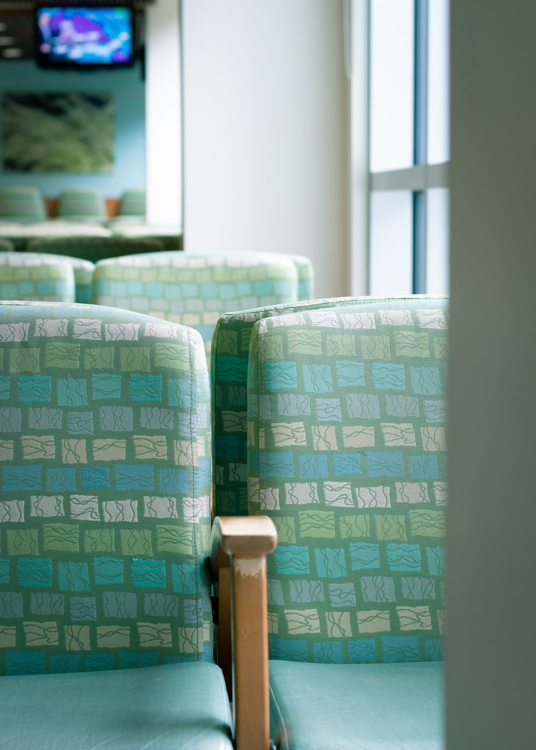 hospital waiting room with green seats next to bright windows and a TV in the distance