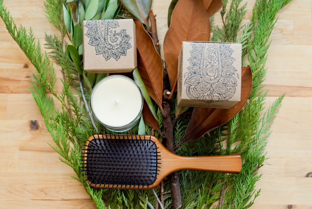 brown wooden hair brush beside white round plate on brown wooden table