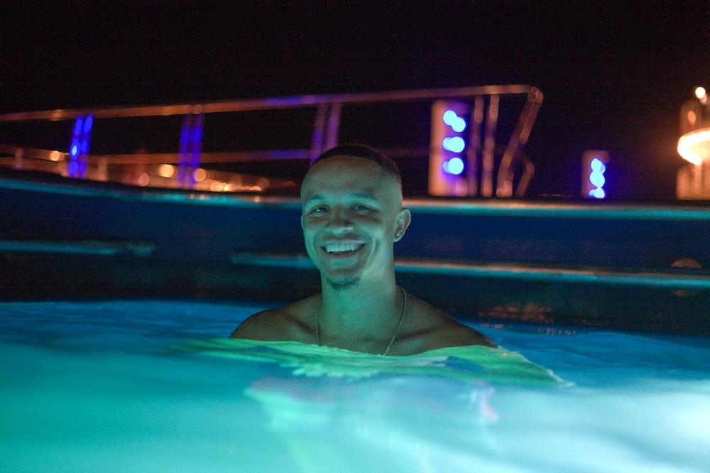 man in swimming pool during night time