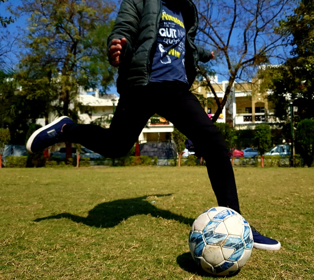 man in blue and white adidas long sleeve shirt and black pants playing soccer during daytime
