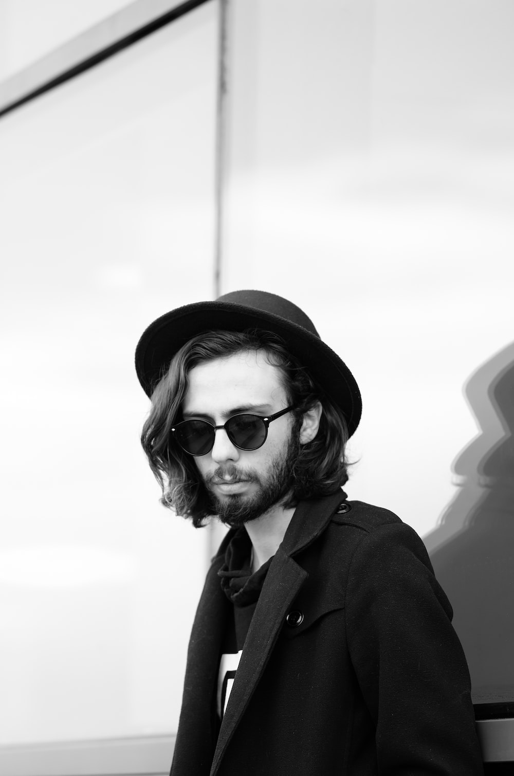 grayscale photo of man wearing sunglasses and hat