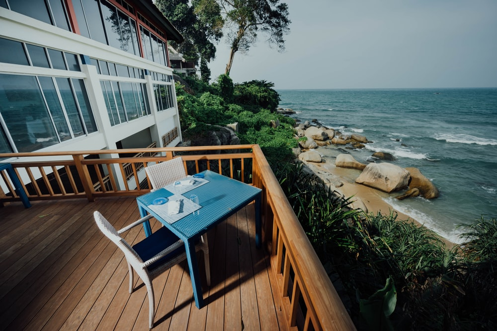 blue and brown wooden table on brown wooden deck near body of water during daytime