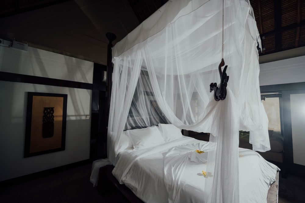white bed linen with black headphones