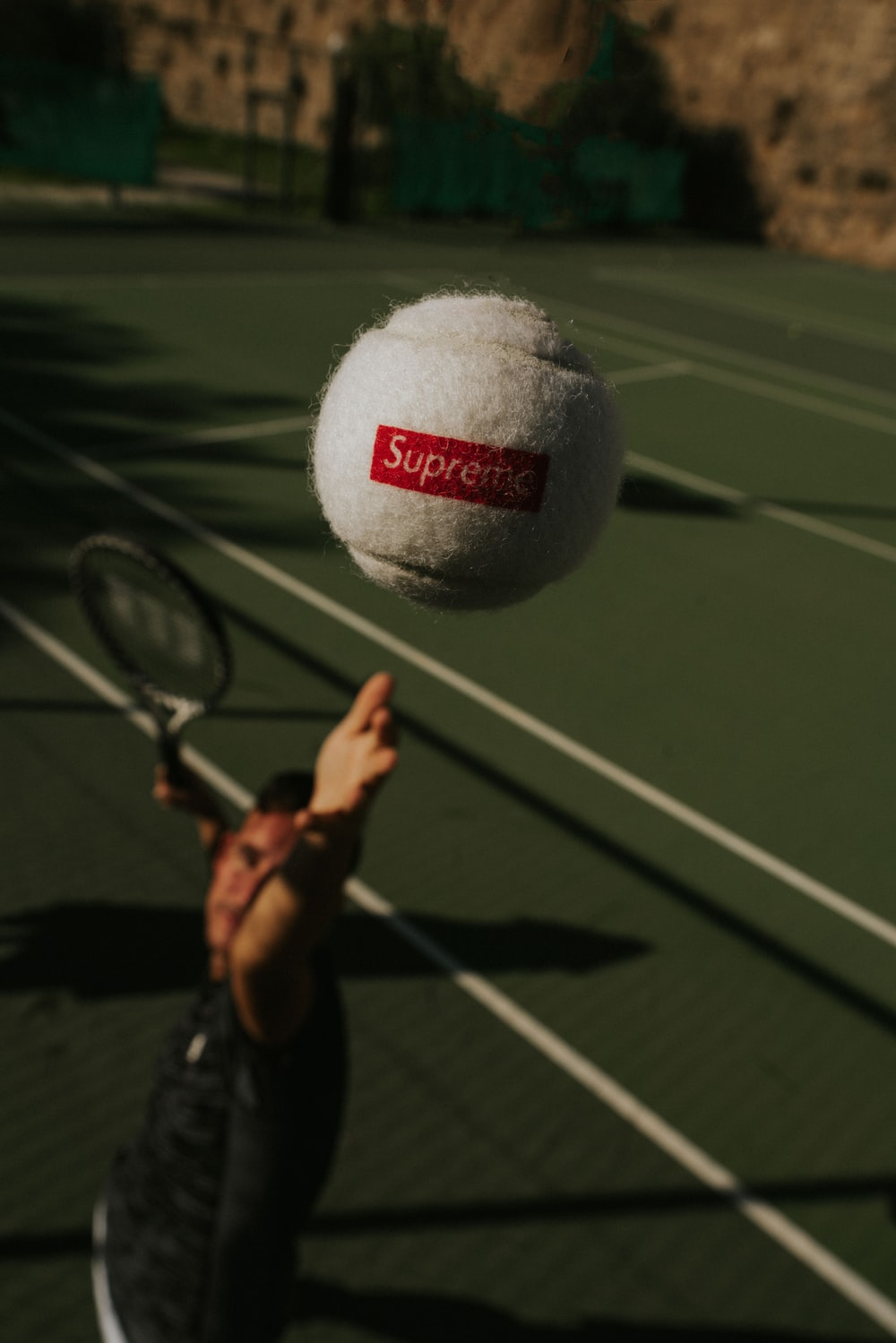 person holding white and red UNK tennis ball