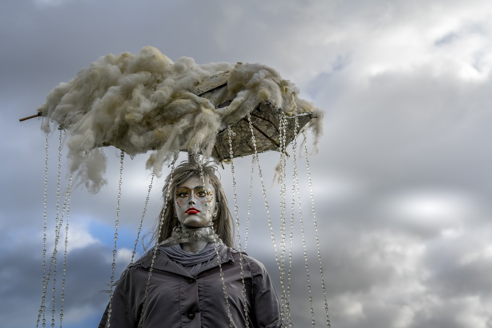 woman in black jacket standing under white clouds during daytime