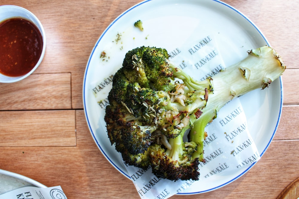 broccoli on white and blue ceramic plate
