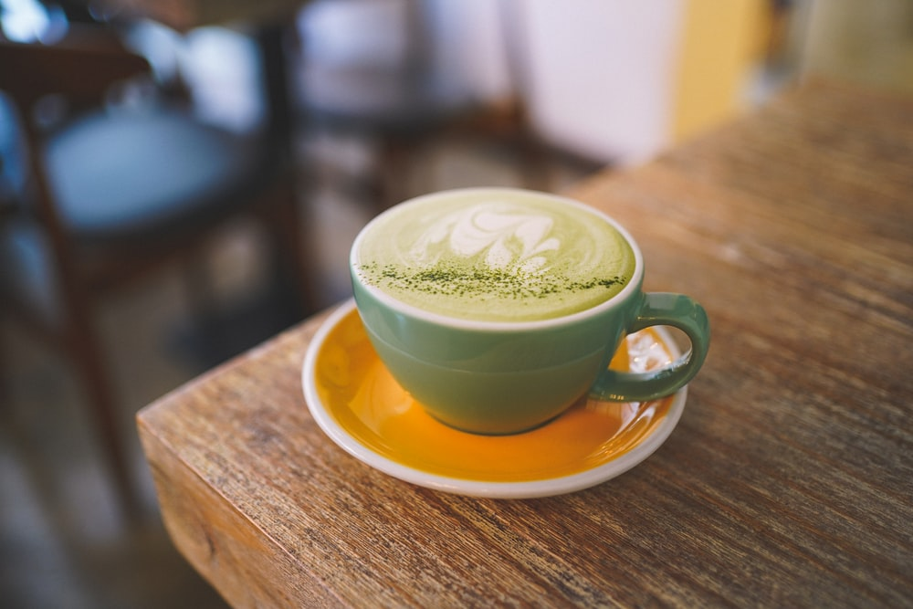 green ceramic mug with saucer on brown wooden table