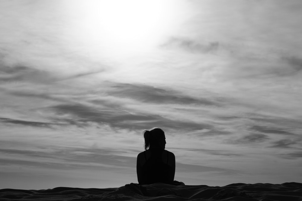silhouette of woman sitting on rock