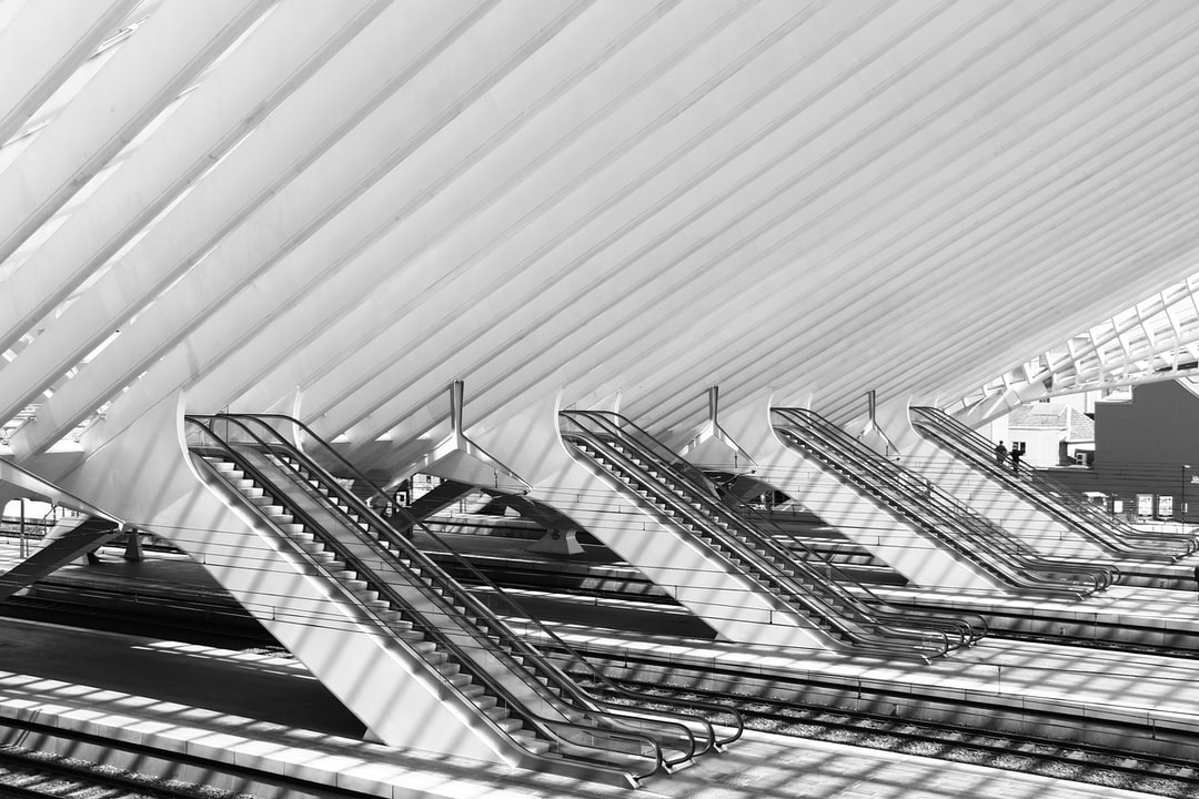 Side view of the escalators in the Liège Guillemins  train station with only two people riding them all the way in the back