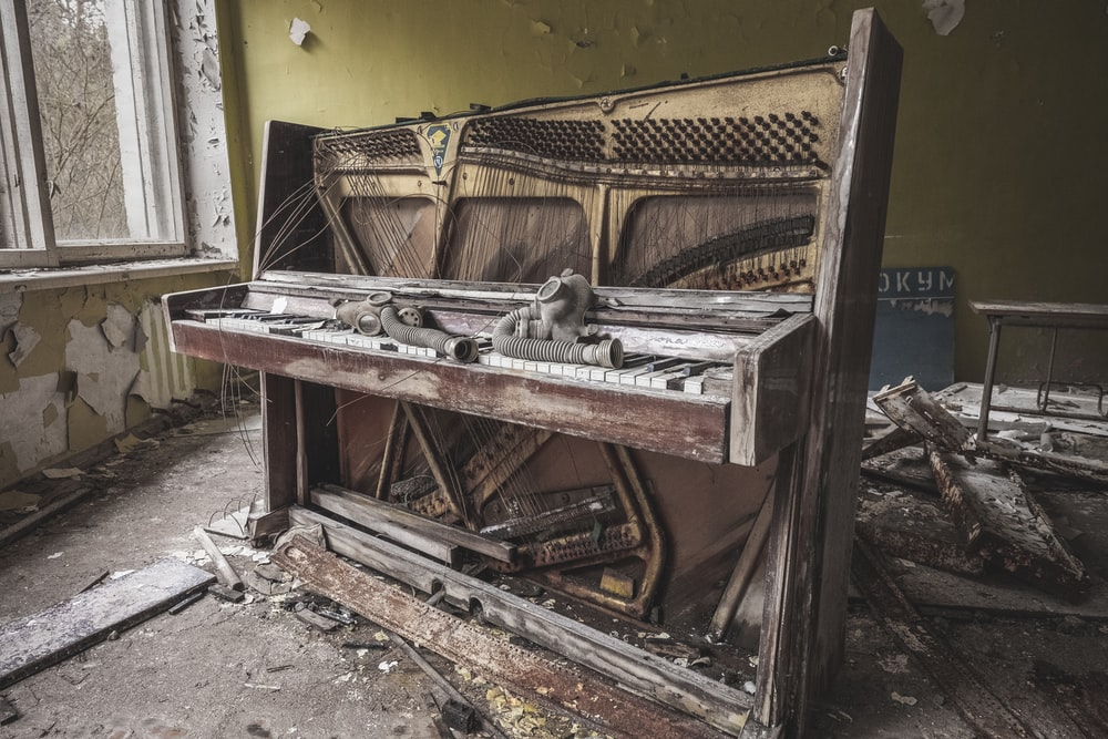 brown wooden piano near yellow painted wall