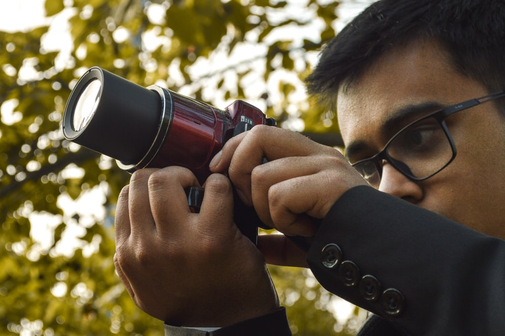 person holding black and red camera during daytime