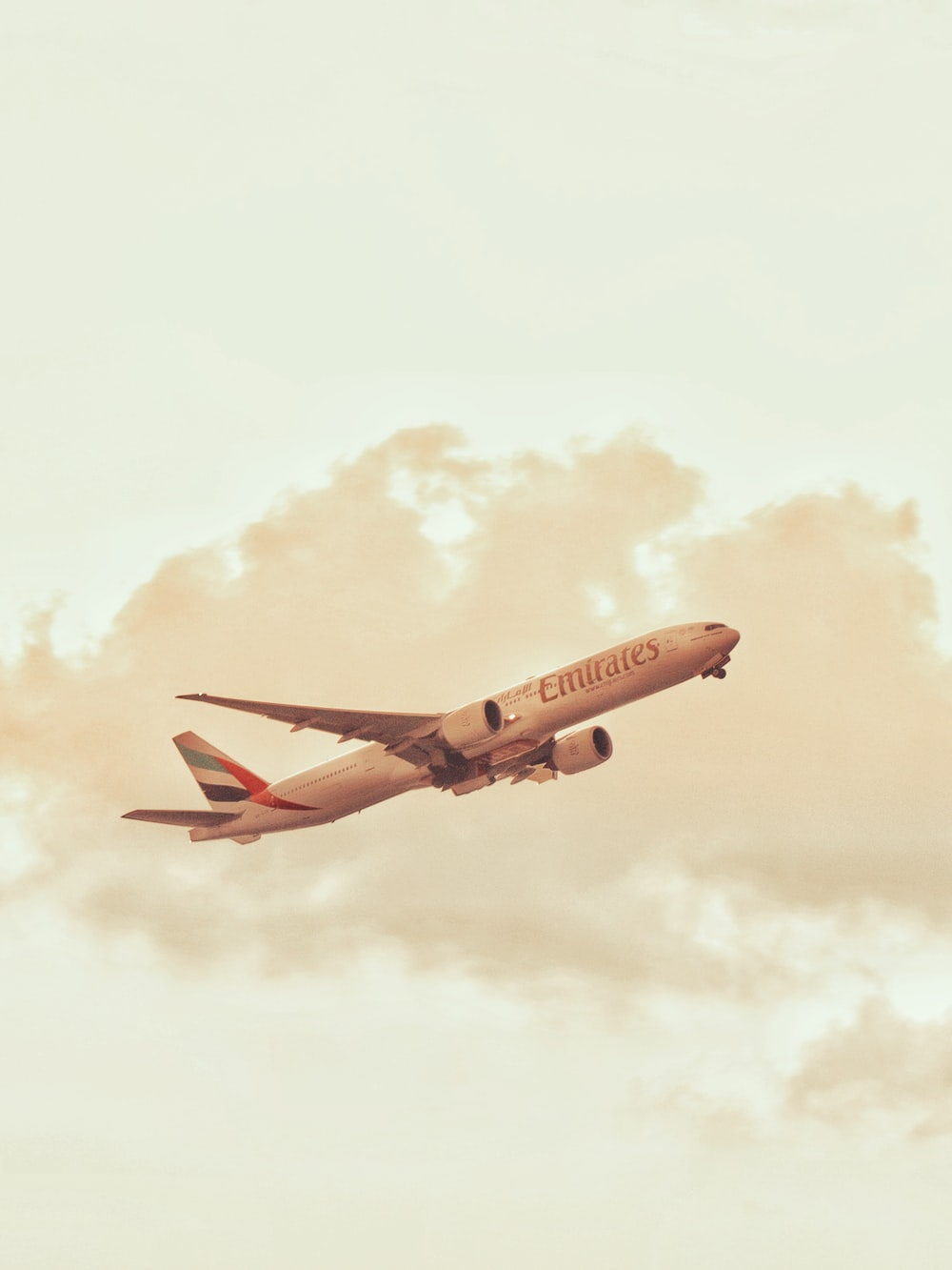 red and white passenger plane flying in the sky during daytime