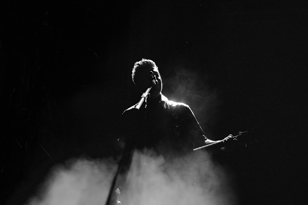 man singing on stage in grayscale photography
