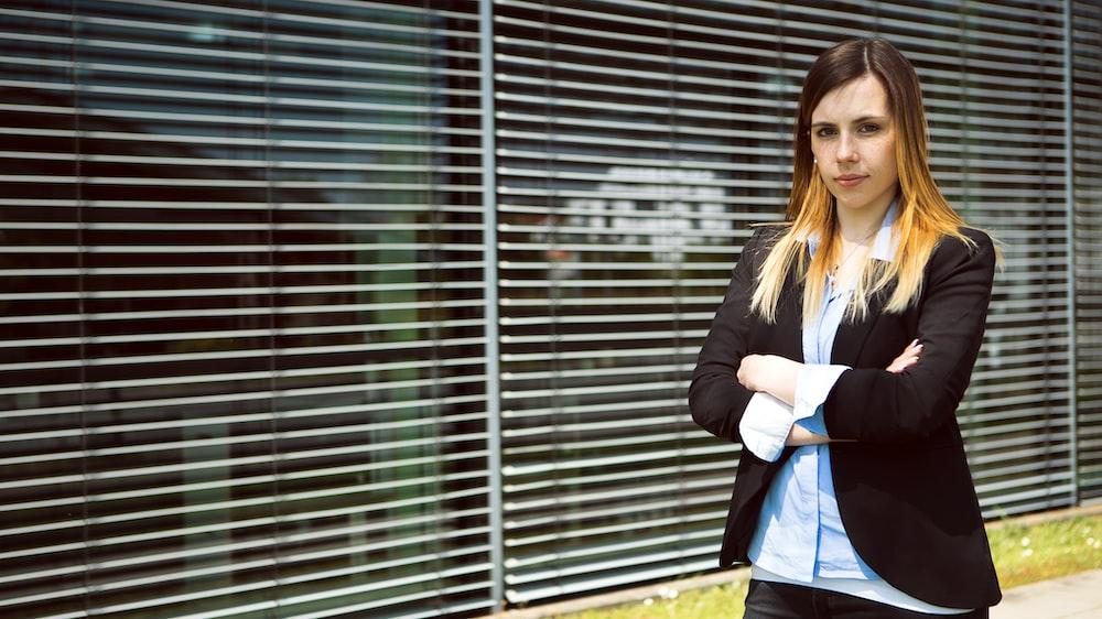 woman in black blazer standing near window blinds