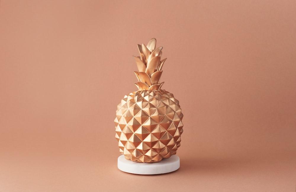 pineapple fruit on white and brown ceramic vase