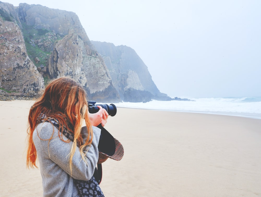woman in brown jacket taking photo of sea during daytime