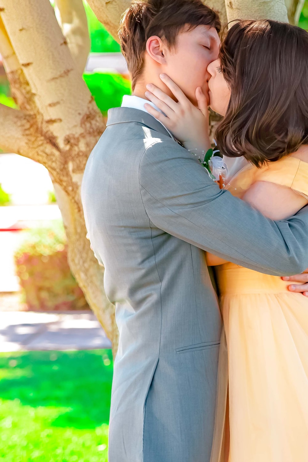 man in gray suit kissing woman in yellow dress