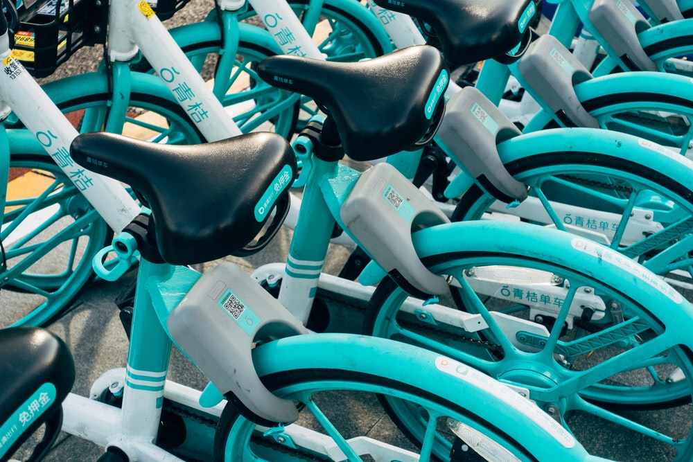 teal bicycle with white plastic bottles