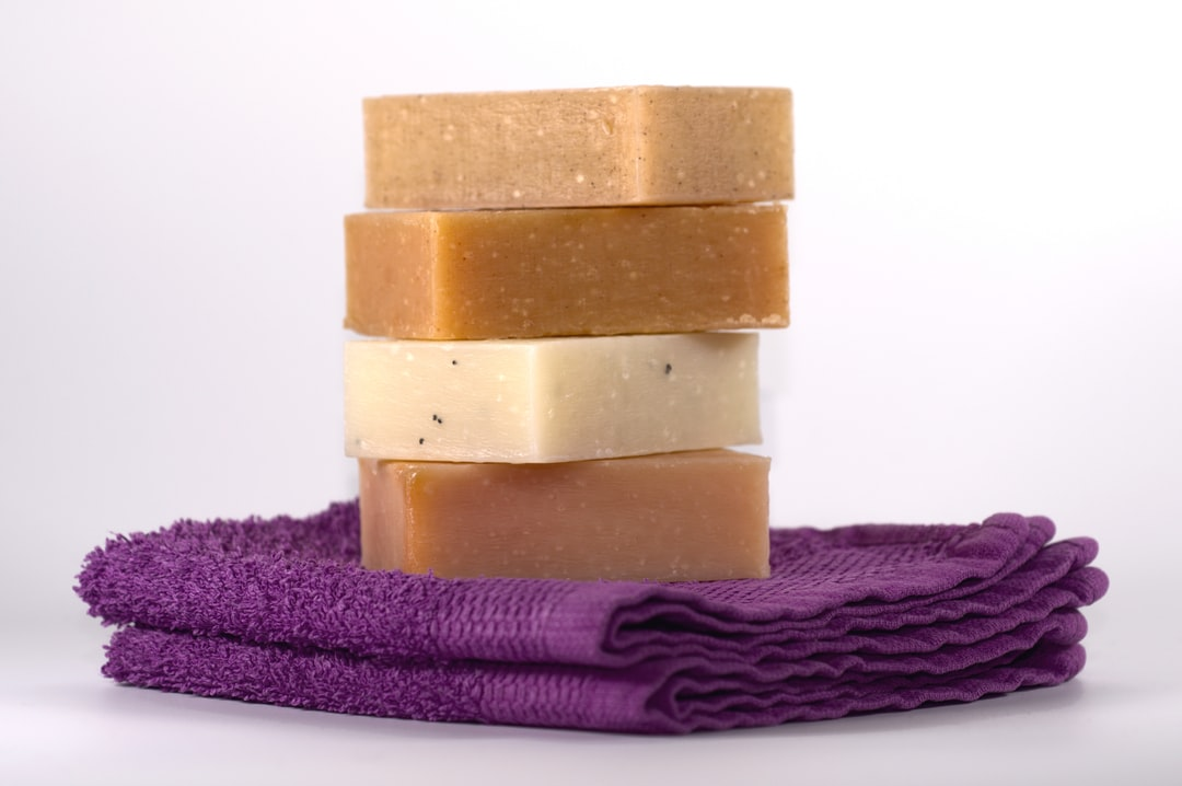 Four bars of hand-made soap on top of two purple coloured washcloths.