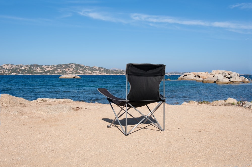 black and gray folding chair on beach during daytime