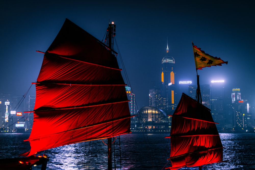 red sail boat on body of water near city buildings during night time