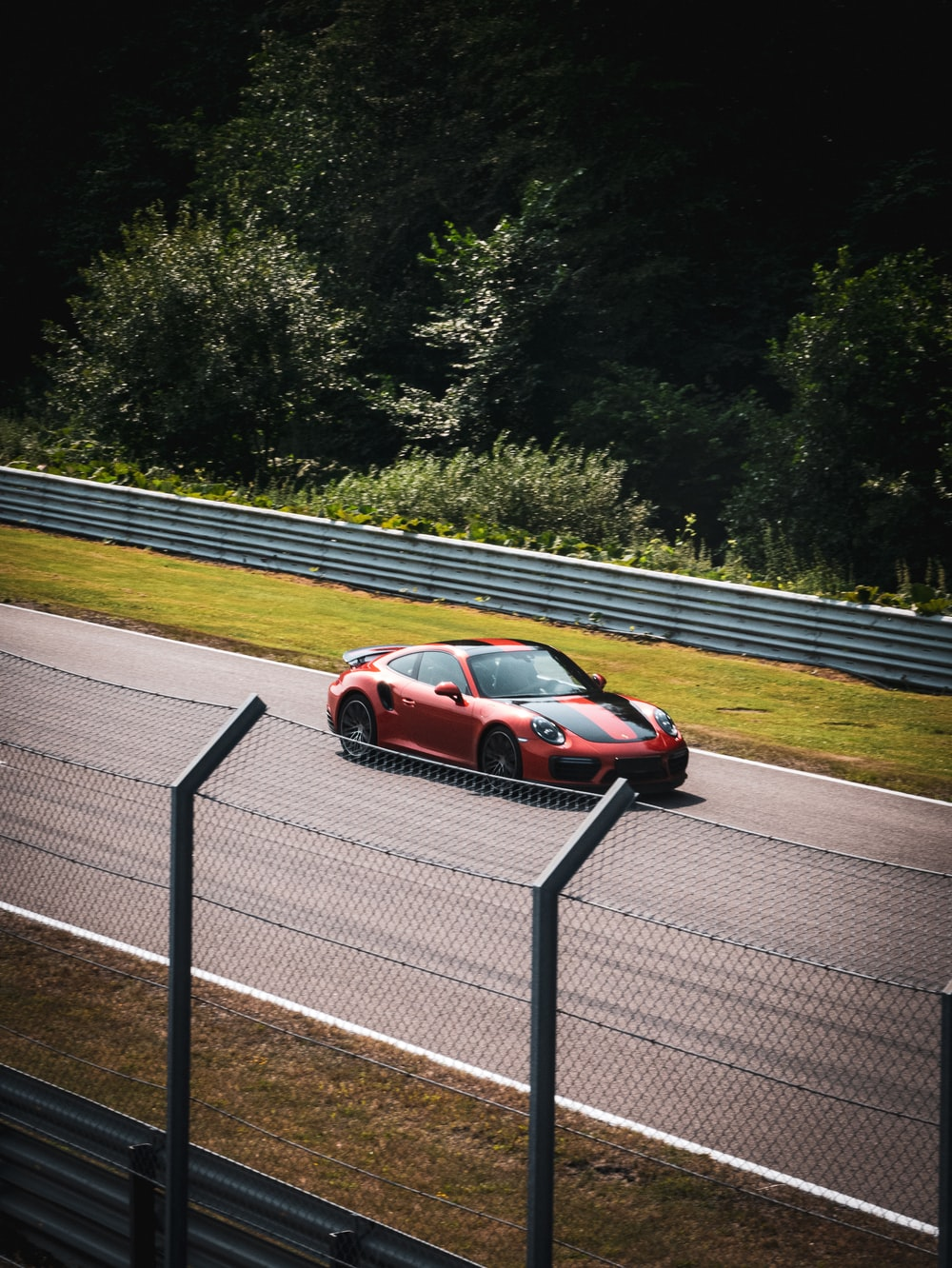 red and black sports car on road during daytime