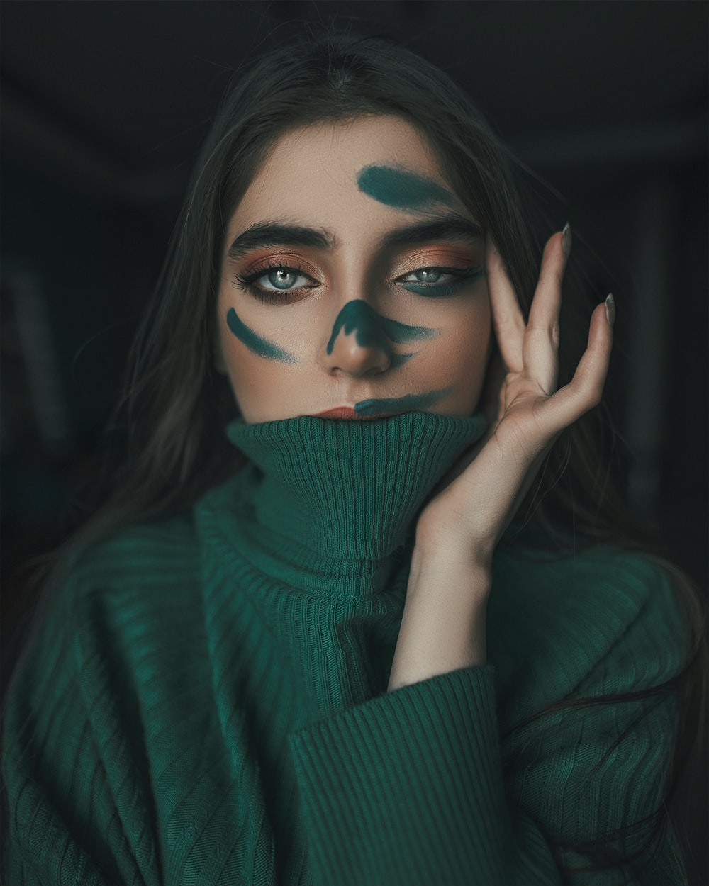 woman in green turtleneck sweater covering her face with her hand