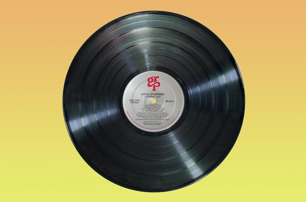 black vinyl record on orange surface