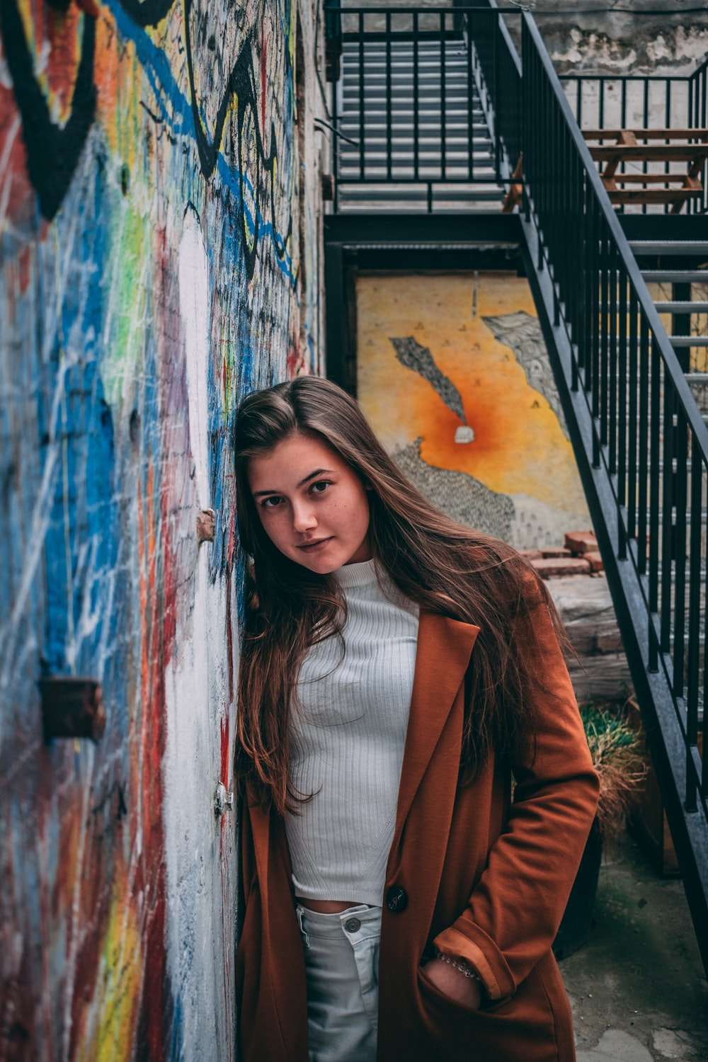 woman in brown blazer standing beside wall with graffiti