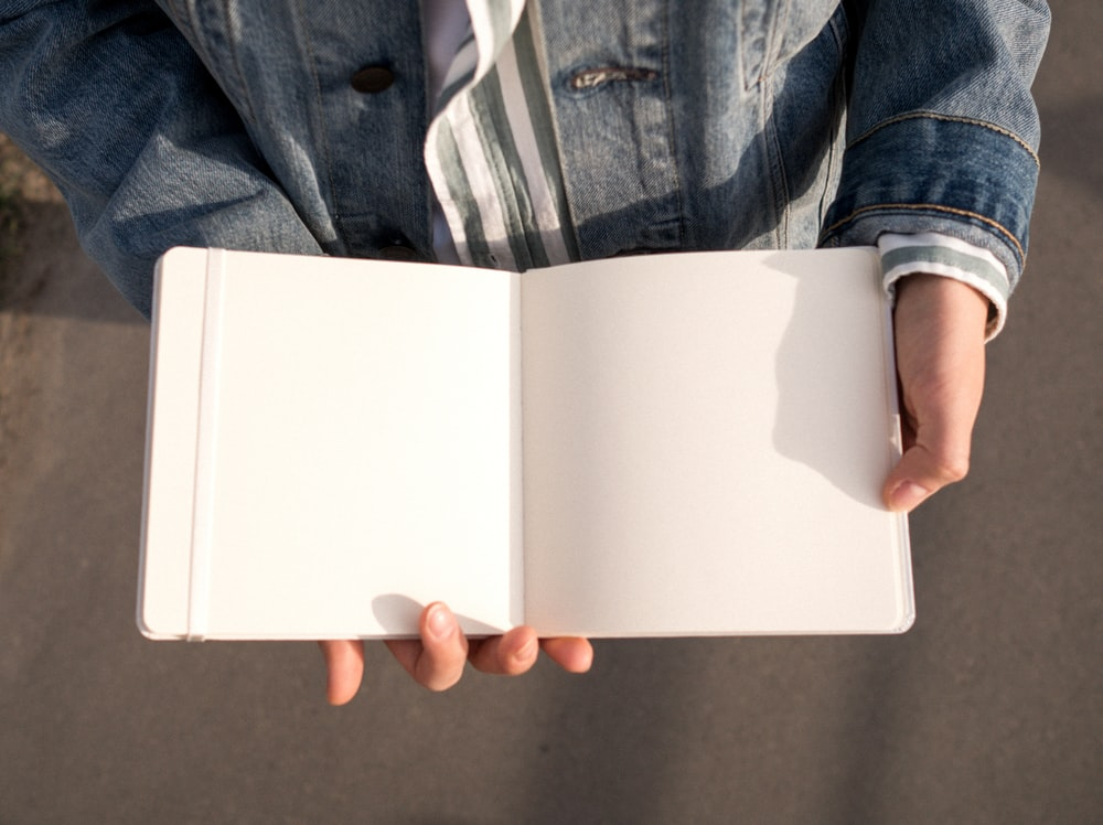 person holding white rectangular box