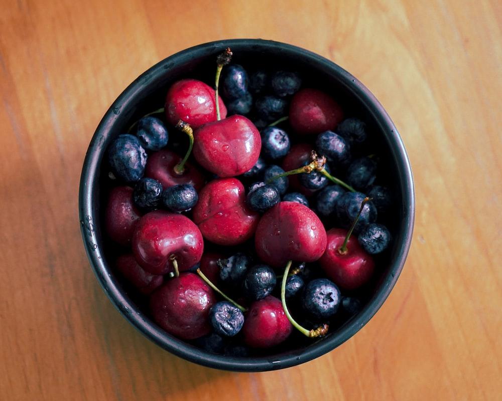 red and black berries in black ceramic bowl