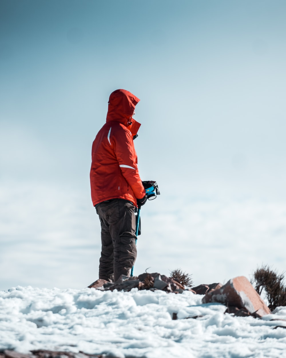 person in red hoodie and black pants standing on snow covered ground during daytime