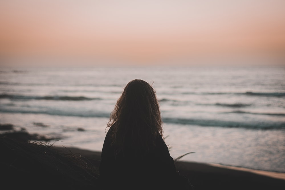 woman in black shirt sitting on beach during sunset