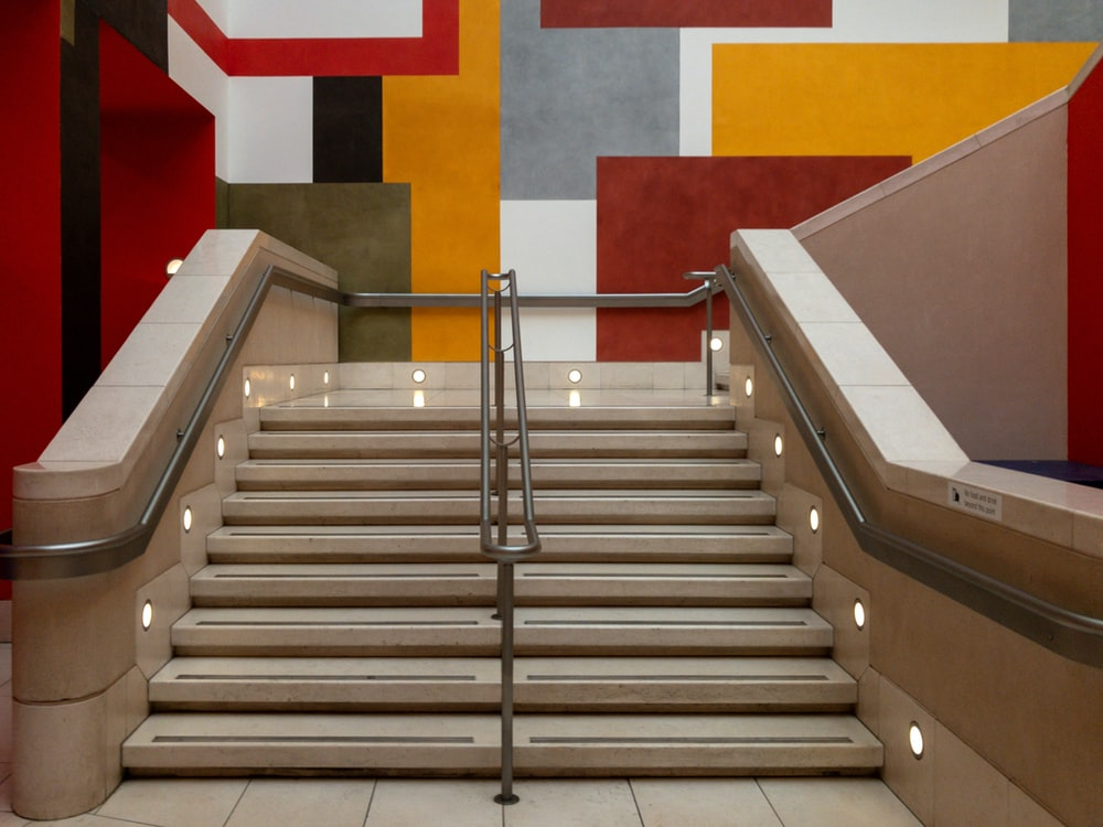 stainless steel hand rail on white and red concrete staircase