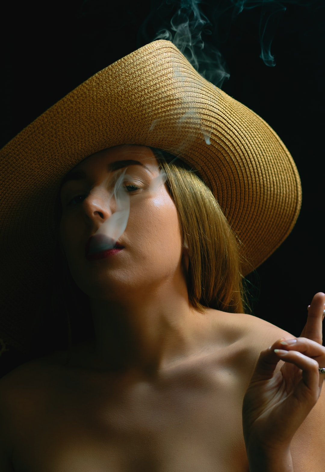 Girl smoking with floppy hat looking at camera side on