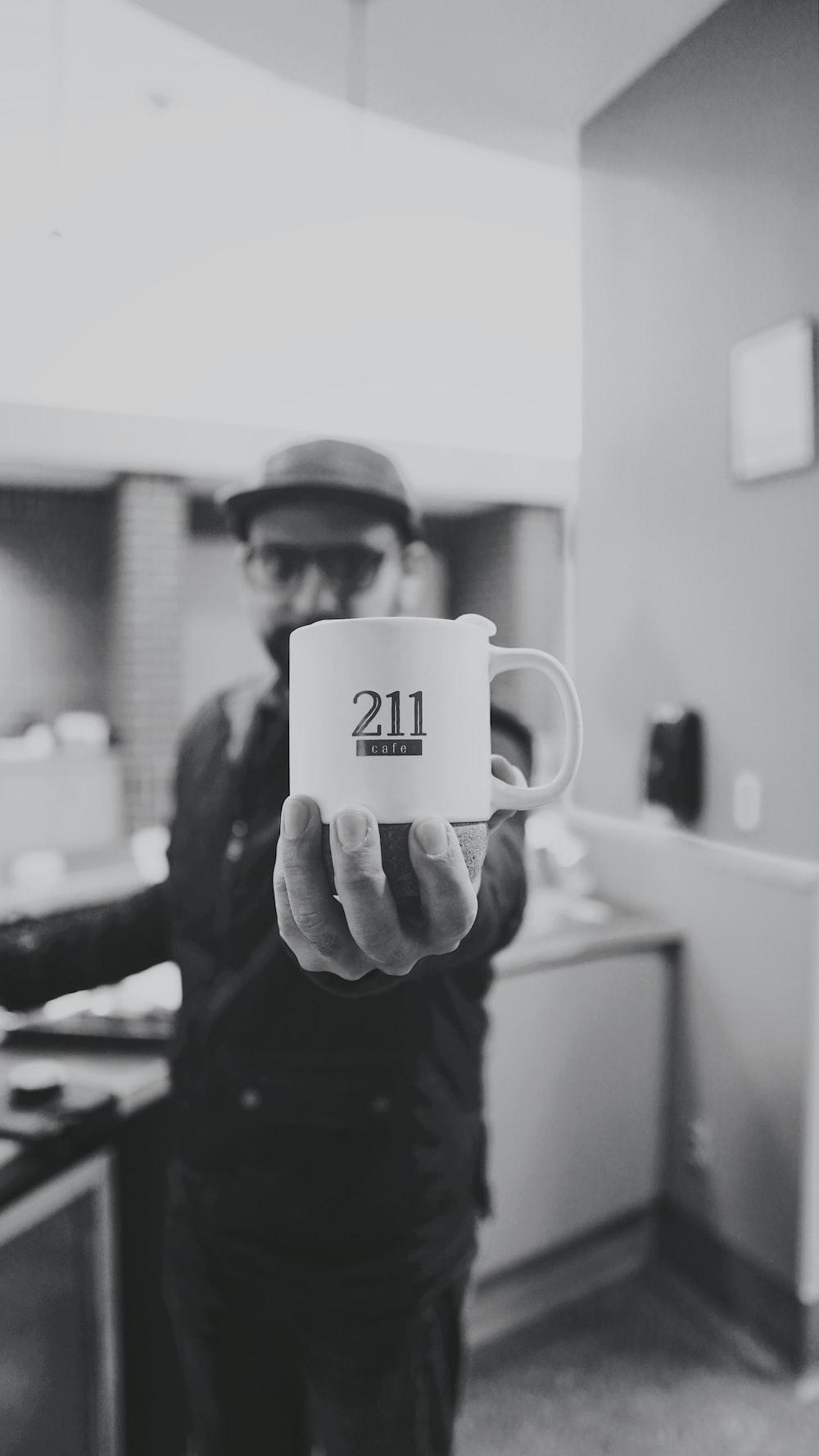 grayscale photo of man holding ceramic mug