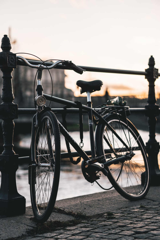 black bicycle on black metal fence during daytime
