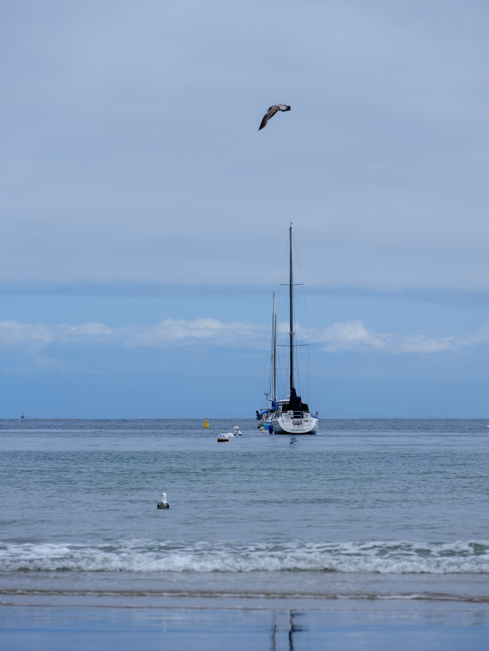 white and black sailboat on sea under white clouds during daytime