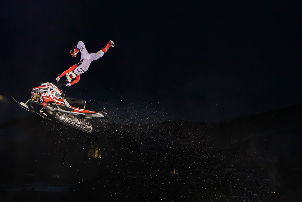 man in red jacket and white pants riding on red and white snowboard during nighttime