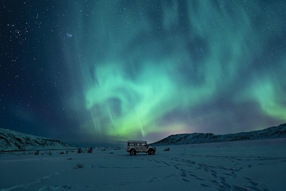 black suv on snow covered field under green aurora lights