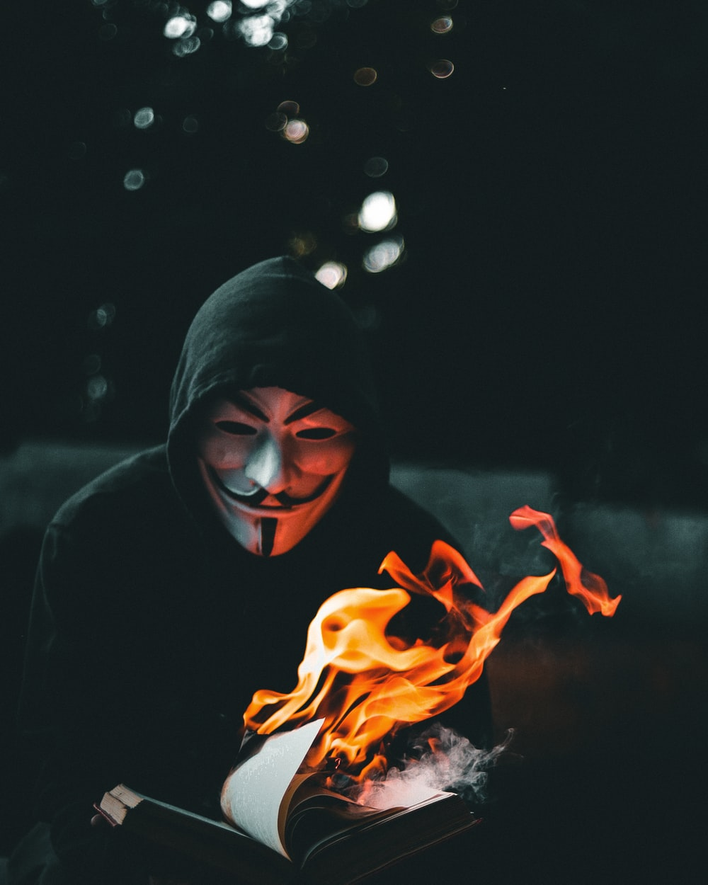 person in black hoodie with orange flame in the background