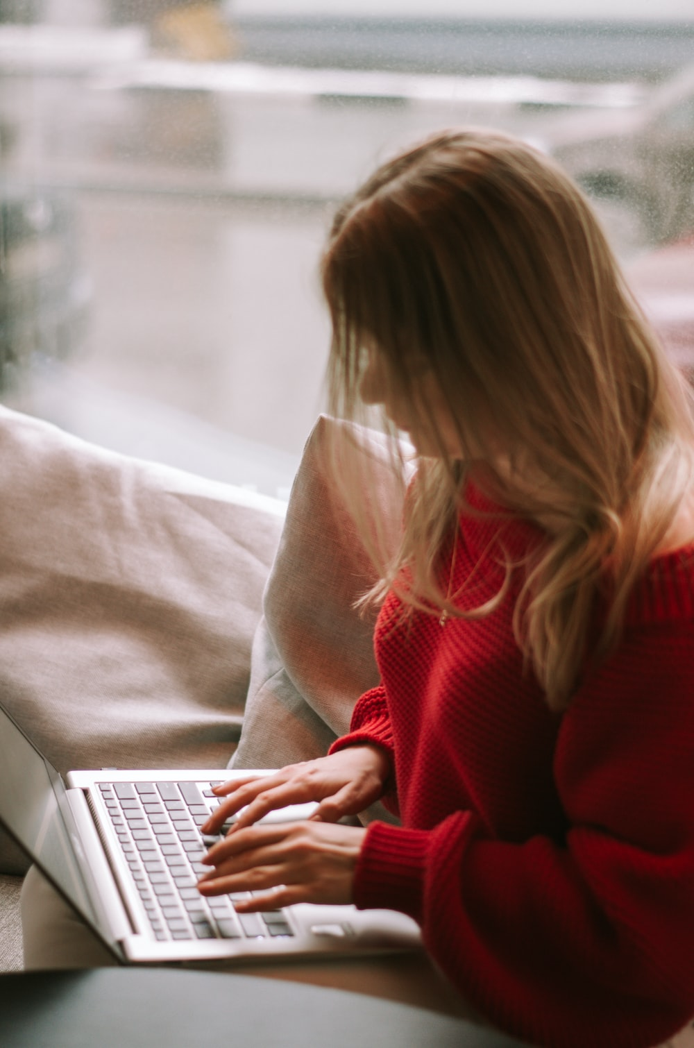 woman in red sweater using macbook air