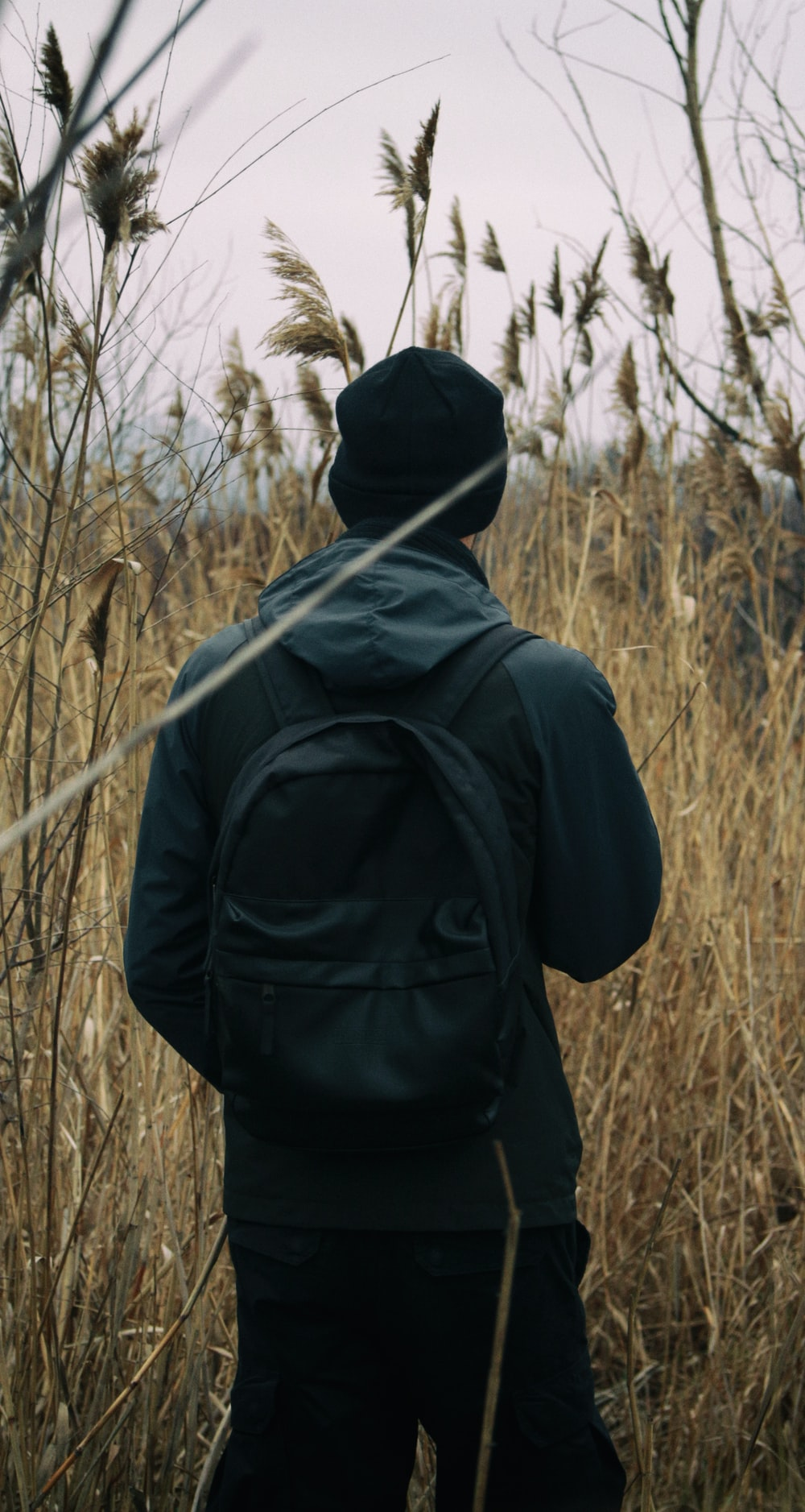 person in black hoodie standing on brown grass field during daytime
