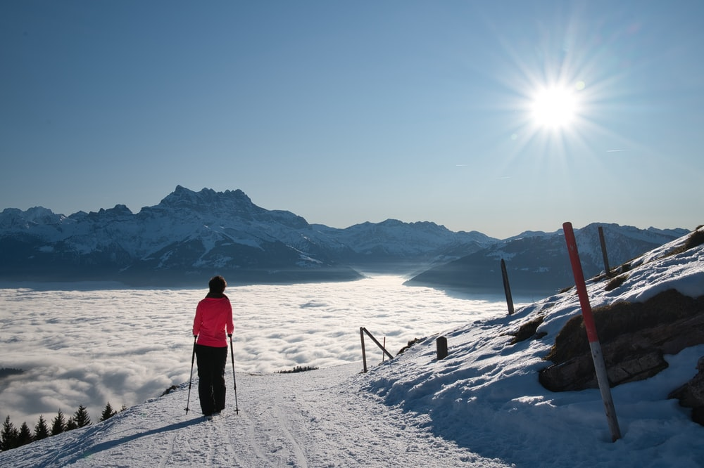 person in red jacket and black pants standing on snow covered ground during daytime
