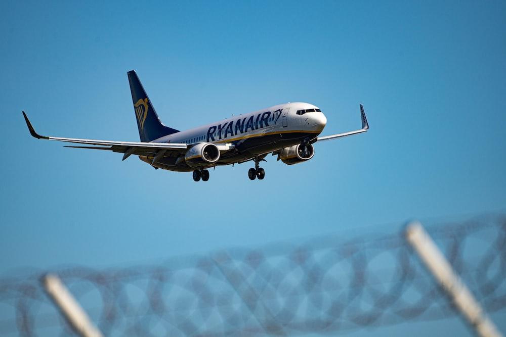white and blue passenger plane in flight