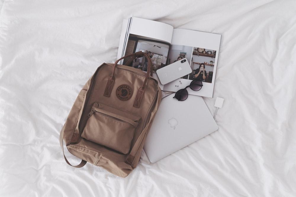 silver ipad beside brown leather handbag