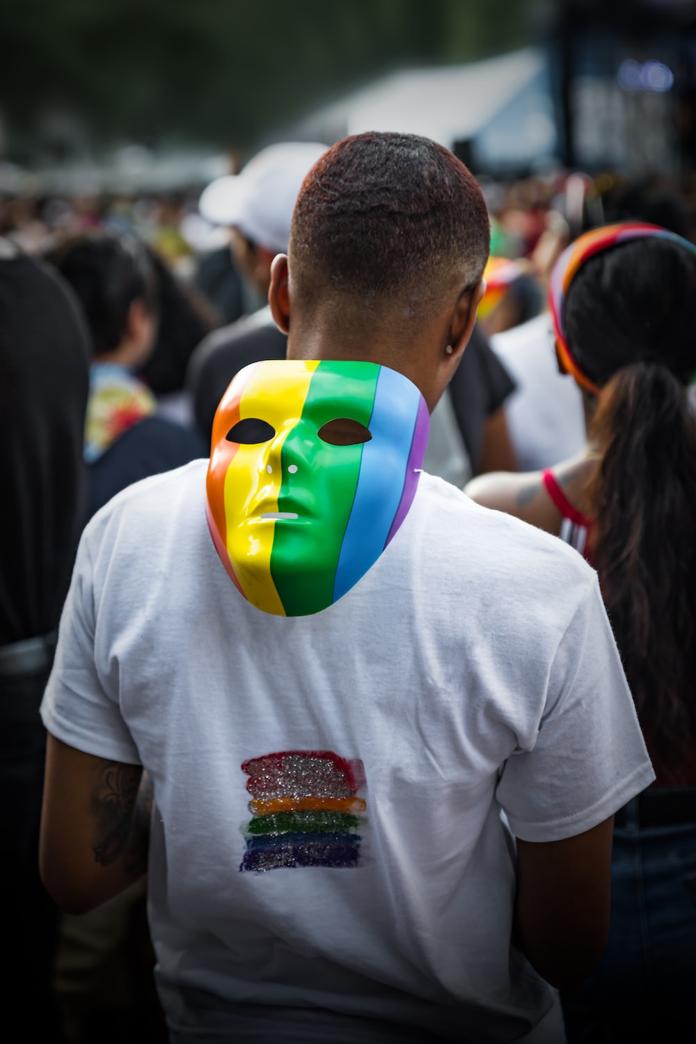 man in white t-shirt with yellow green and red face mask
