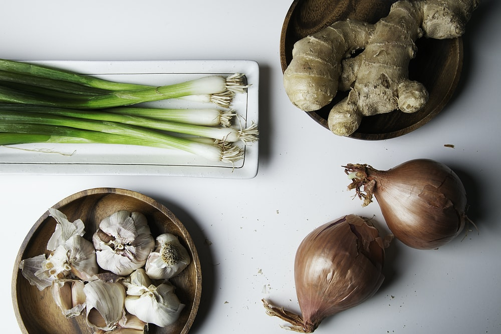 brown garlic on white chopping board